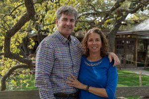 White middle aged couple with arms around each other, standing in front of tree
