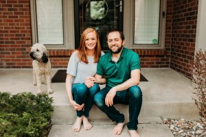 Young white couple, red headed woman, dark haired man with beard, holding hands, sitting on front porch with their white labradoodle